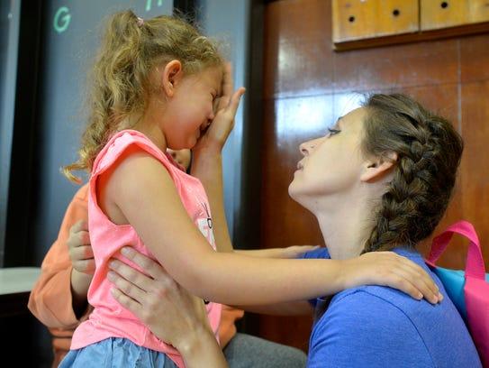 Bridgette Stinson comforts her niece Isabella Stinson,