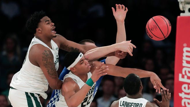 Michigan State forward Nick Ward, left, guard Miles Bridges, center, and guard Joshua Langford (1) vie for a rebound against Kentucky forward Isaac Humphries, rear, during the first half on Tuesday in New York.