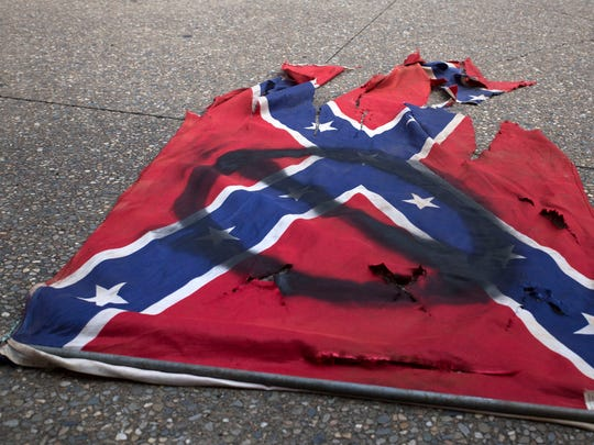 """A defaced confederate flag lays on the ground during the Stand Against Hate rally in Market Square organized by the Women's March Coalition of East Tennessee in Market Square Sunday, Aug. 13, 2017. The demonstration was held in response to yesterday's """"Unite the Right"""" rally in Charlottesville, Virginia, which left three people dead."""