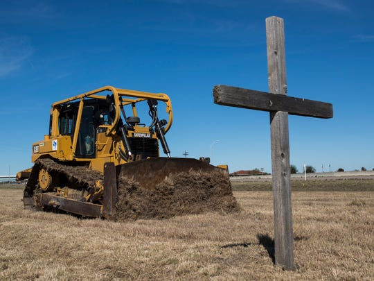 A bulldozer breaks ground for the foundation of the Corpus Christi Cross during a contract signing ceremony Monday, Jan. 29, 2018, near Carbon Plant Road and Interstate 37.