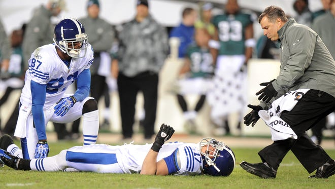 Colts receiver Reggie Wayne kneels next to Austin Collie after the vicious hit he suffered in a 2010 game against the Eagles.