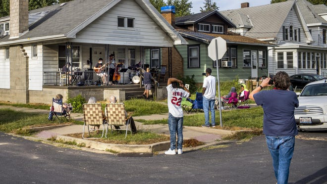Jazz fans begin to gather on East Kansas St. Saturday, Aug. 29, 2020 for the first of a series of Porch Concerts initiated by musician David Hoffman. With Hoffman on trumpet and keyboards, left, Mike Nellas on guitar, Jamika Russell adding vocals, Steve Jackson on bass and Jason Brannon on drums, Hoffman began the series as a fundraiser for area musicians whose work has been reduced by the pandemic.