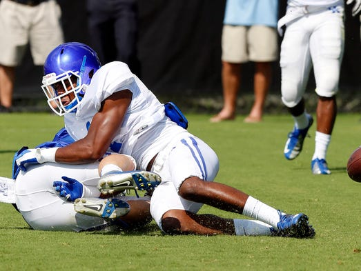Kentucky's A.J. Stamps, top, practices on campus in Lexington.  Aug. 12, 2014