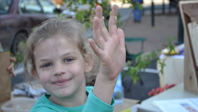 Katelyn Penney shows off her peanut butter and bird seed covered fingers after making a bird feeder at Earth Day Staunton. The 6-year-old from Weyers Cave visited the event with her family on Saturday.