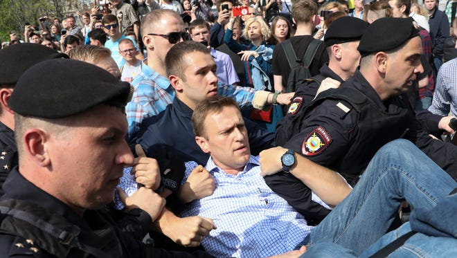 Russian police carrying struggling opposition leader Alexei Navalny, center, at a demonstration against President Vladimir Putin in Pushkin Square in Moscow, Russia, May 5, 2018.