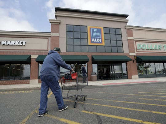 A customer approaches the entrance of an Aldi food market, in East Rutherford, N.J., in this May 31, 2017, photo. The discount grocery retailer is opening a regional office and distribution center in Gilbert, and Arizona stores are expected to follow.