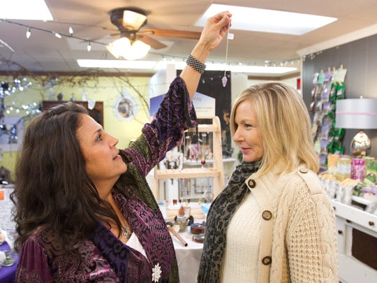 Cathy Boaz,left, owner of Kokopelli's Korner in downtown Howell, uses an amethyst pendulum to read the openness of Dianna O'Grady's chakras. O'Grady conducts readings and teaches intuitive development classes at the store.