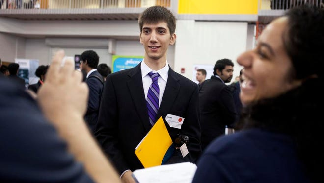 Rochester Institute of Technology student James Brunner looks to a sign language interpreter with visiting with representatives from Qualitrol, a Fairport company.