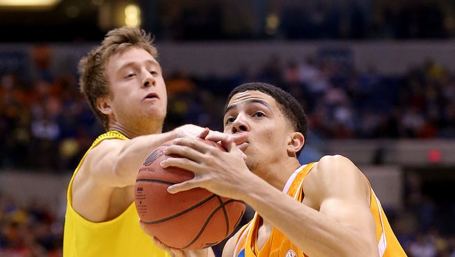 Michigan's Spike Albrecht, left, fouls Tennessee's Darius Thompson during a Midwest Regional NCAA Men's Basketball Championship game March 28, 2014 at Lucas Oil Stadium.