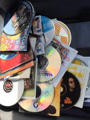 A pile of CDs on my passenger seat shows albums by