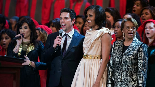 First lady Michelle Obama, second from right, and her mother Marian Robinson join singers Demi Lovato, from left, Chris Mann and other performers, during the Annual Christmas in Washington presentation at the National Building Museum in Washington, Sunday, Dec. 9, 2012.