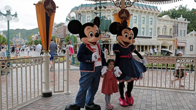 """FILE - In this June 10, 2016, file photo, a girl poses with Mickey and Minnie Mouse at the Hong Kong Disneyland in Hong Kong. Hong Kong officials said Tuesday, Nov. 22, 2016 they signed an agreement for a $1.4 billion expansion of the southern Chinese city's Disneyland theme park. The government said the plan calls for adding two new themed areas, based on the movie """"Frozen"""" and characters from """"Marvel Super Heroes,"""" to Hong Kong Disneyland."""