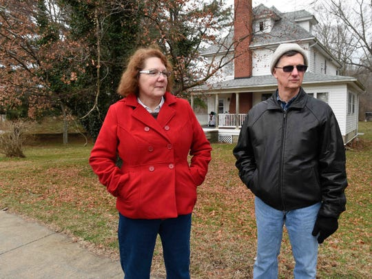 Amy and Bob Weissenfluh stand in front of their home in Hartly, a town which has no government. No taxes have been collected and the town is in debt.