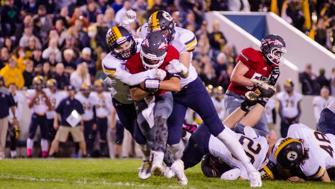 #3Port Huron High School QB John Oriel is brought down by players from Port Huron Northern during the Crosstown Showdown football game Oct. 20.