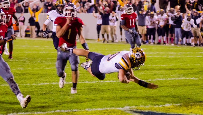 Port Huron Northern High School's QB dives into the end zone for a touchdown, bringing the Huskies up 21-7 over Port Huron High School during the Crosstown Showdown football game Oct. 20.