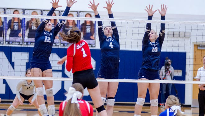 Marysville's Hayley Delor (12), Paige Fraley (4) and Hannah Delor (10) jump to block a hit by St. Clair's Jessica Bohm during the MHSAA Class B District Volleyball Finals at Marysville High School Nov. 3.