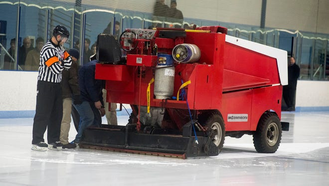Referees and maintenance crew work to move a broken-down Zamboni off the ice during one of the Silver Stick Finals matches at Glacier Pointe Ice Complex Jan. 5.