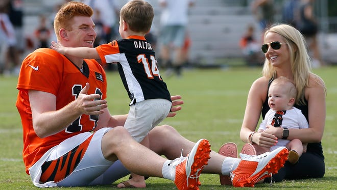 Cincinnati Bengals quarterback Andy Dalton (14), left, plays with his son Noah as Jordan Dalton holds Nash after Cincinnati Bengals training camp practice, Tuesday, Aug. 8, 2017, on the practice fields next to Paul Brown Stadium in Cincinnati.