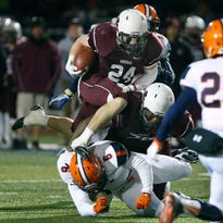 State semifinals: Aquinas' Jamir Jones is tackled by Liverpool's Daryl Nixon jr. as he tries to gain yards in the second quarter at North Syracuse High School.