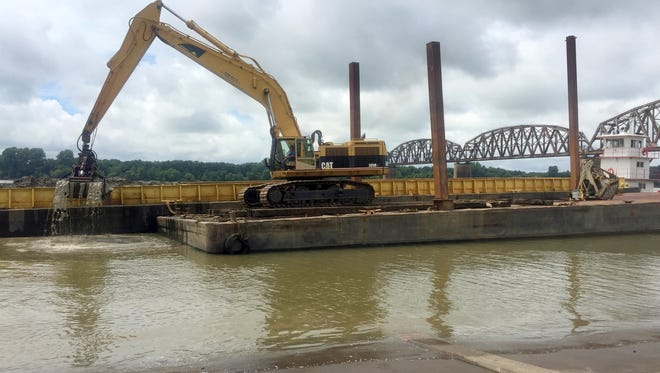 In this file photo, workers on a barge use an excavator to clean silt and mud from the boat ramps at the Henderson Riverfront. That work is expected to begin again sometime around Wednesday, Aug. 7.