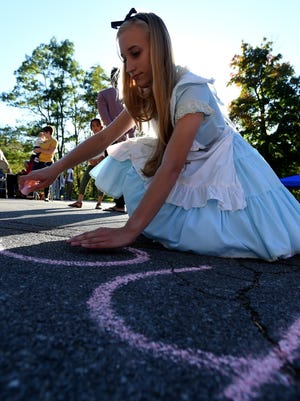 """Lily Ballenger draws as """"Alice"""" from the Richmond Civic Theatre production of """"Alice in Wonderland"""" Saturday, Oct. 8, 2016 during the annual City Life celebration at Glen Miller Park in Richmond."""