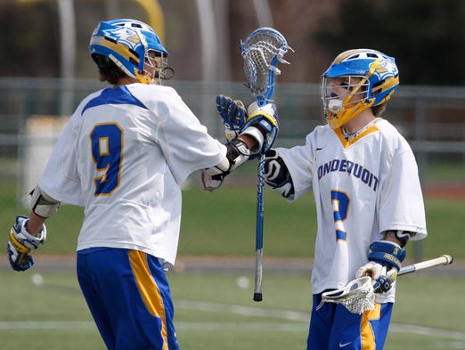 Irondequoit's Andrew Knope, right, celebrates his first-quarter goal with teammate Daniel Doktor, left, during the April 18 game against Geneva.