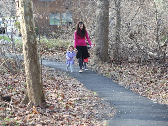 A young woman with two small children walk on an illegally