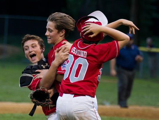 Holbrook pitcher Tai Mann is hugged by teammates as