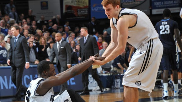 Butler's Erik Fromm helps teammate Khyle Marshall up from the floor after The Villanova Wildcats beat the Butler Bulldogs 76-73 in overtime in the Bulldogs' Big East debut at Hinkle Fieldhouse Tuesday December 31, 2013.