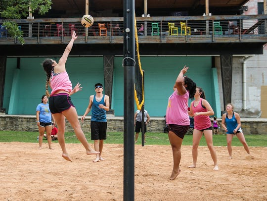 Participants play volleyball during the summer grand