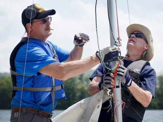 Curtis Boyd, left, and Bob Mitchell prepare to hoist their sails before competing in the Southern Comfort Regatta at Lake Julian April 29, 2017.