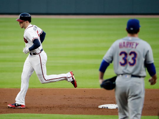 The Atlanta Braves' Freddie Freeman, left, rounds the bases after hitting a two-run home run off Mets starting pitcher Matt Harvey, right, during the first inning Tuesday.