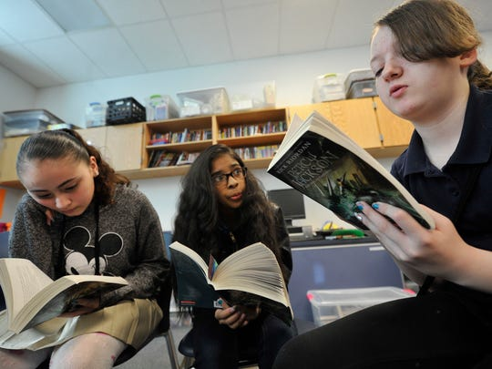"""From left: Esmeralda Machado, Jackeline Gonzalez and Halie Brackbill, fifth graders at Jackson K-8 school, take turns reading  """"Percy Jackson"""" during a small group reading session on Friday."""