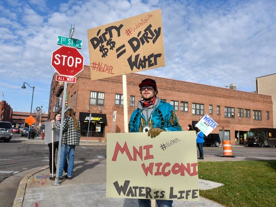 Protesters hold signs in opposition to funding for the Dakota Access pipeline Tuesday, Nov. 15, in front of the Wells Fargo Bank building in downtown St. Cloud.
