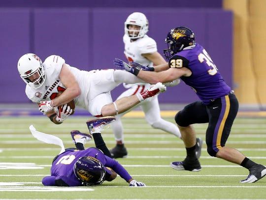 Northern Iowa's Malcolm Washington and Duncan Ferch, right, tackle South Dakota's Brett Samson.