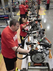 Assembly line workers build a 2015 Chrysler 200 automobile