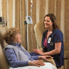 Molly Downhour (right), Operations Director of the Virginia G. Piper Cancer Center Clinical Trials, visits with a clinical trial patient.