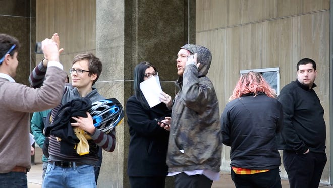 Associates of the People's Solidarity Rally protesters who were arrested in connection with an alleged assault on a photographer clash with reporters outside Rochester City Court on Monday, Jan. 23, 2017