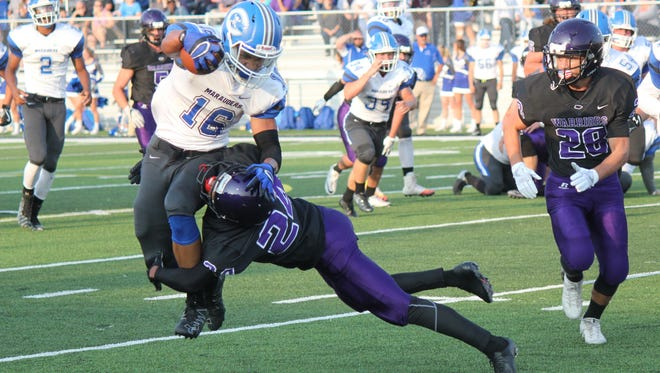 Woodhaven's Thomas Conley hits Gibraltar Carlson running back Brandon Stewart on a first-half play on Friday, Aug. 25, 2017.