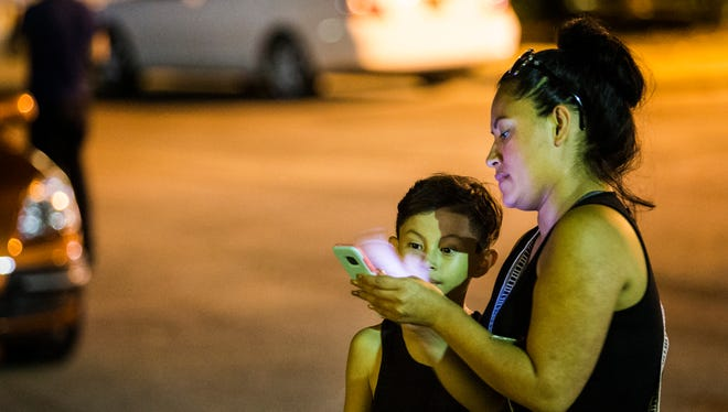 """Jeanette Perez shows her eight year-old son Phu Nguyen a Pokemon as she tries to catch it near the Delaware Children's Museum in Wilmington on Tuesday night. """"I used to bully my brother because he played it,"""" Perez said. """"It started as a joke, now this is our bonding."""""""