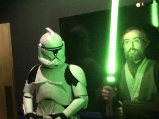 """Carl Grasso of Fairfax wields a light saber Thursday before the first screening of """"Star Wars: The Force Awakens"""" at Essex Cinemas."""