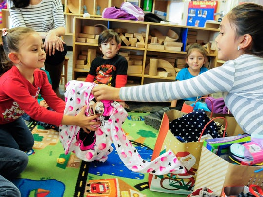 Lillyanna Martinez, 10, right, gives Minnie Mouse pajamas to Valeria Acosta, 5, at Jardin de los Niños on Thursday. Martinez , whose celebrated her birthday Nov. 21, decided to give gifts to less fortunate children rather than receive birthday presents. Martinez donated more than 40 items.
