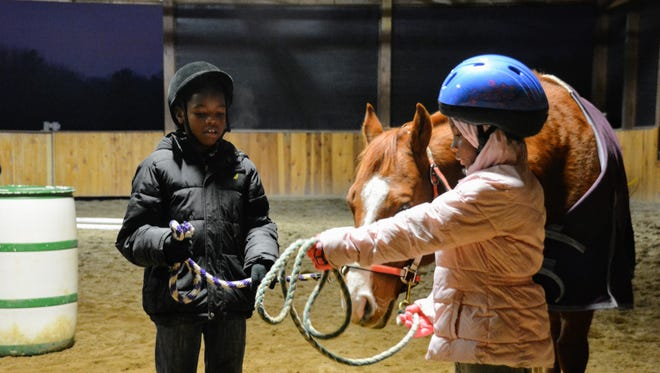 Travon Hartwell, 8, and Ayanna Jetton, 8, lead a horse through an arena.