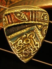 The antique Mayan embossed/enameled brass guitar pick
