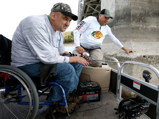 Army veteran Tony Miller, who broke his neck when he dove into a shallow lake leaving him paralyzed from the neck down, with only limited use of his arms, fishes using a custom-made, electric-powered reel designed by Fishing Dreams for Veterans founder J. P. Snell, right, on Wednesday, Nov. 2, 2016.