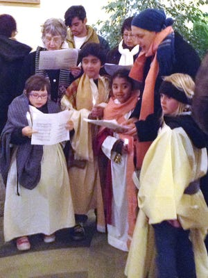 Mary and Joseph, portrayed by children, are welcomed at the Murray Hotel on Wednesday during the Las Posadas procession. The event was held by the Episcopal Church of the Good Shepherd.