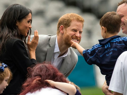 A toddler strokes Prince Harry's beard as Duchess Meghan