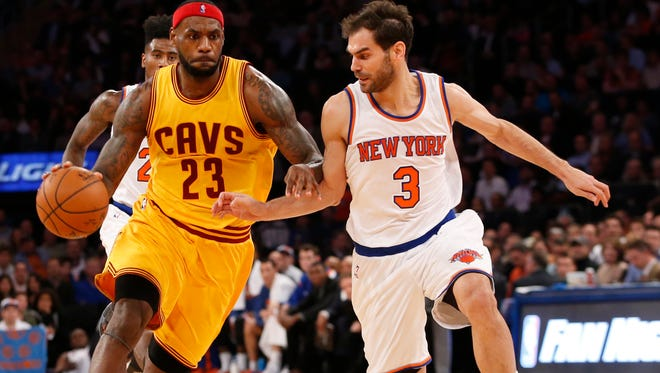Cleveland Cavaliers forward LeBron James drives toward the basket with New York Knicks guard Jose Calderon in the first half of an NBA basketball game at Madison Square Garden in New York, Thursday, Dec. 4, 2014.