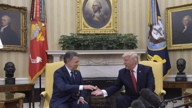 President Donald Trump reaches to shake hands with Colombian President Juan Manuel Santos in the Oval Office of the White House in Washington, Thursday, May 18, 2017.