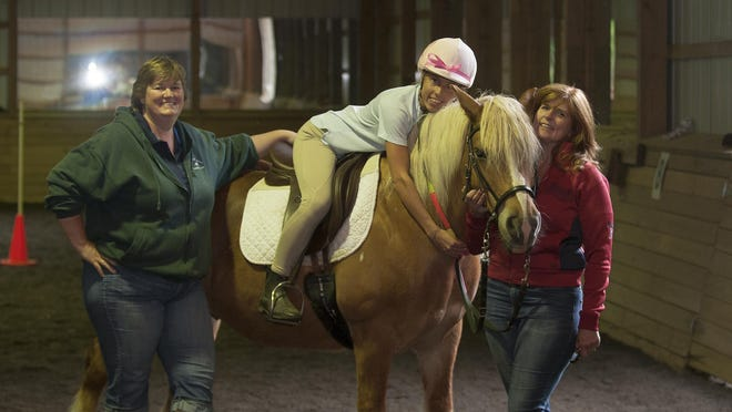 Volunteer Jo Holberg, left, trainer Sherri Briggs, right, with rider Bridgid Cain and horse Cocoa during a lesson at Compassionate Friends Therapeutic Riding Center in Medford in 2015.